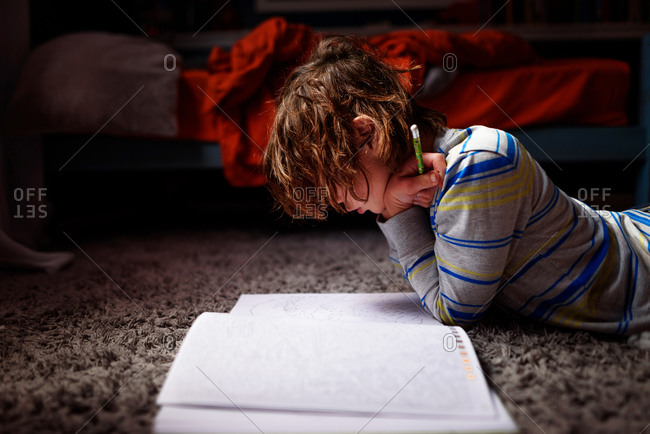 A young boy doing homework on the floor