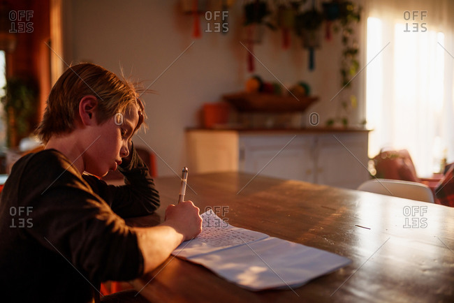 A young boy writing in a journal at the dining table