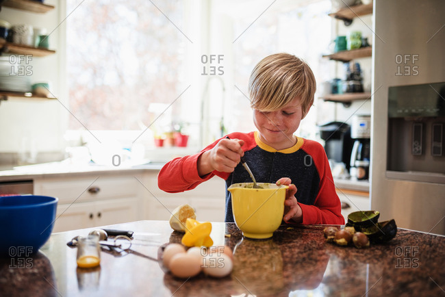 A young boy making lunch in the kitchen