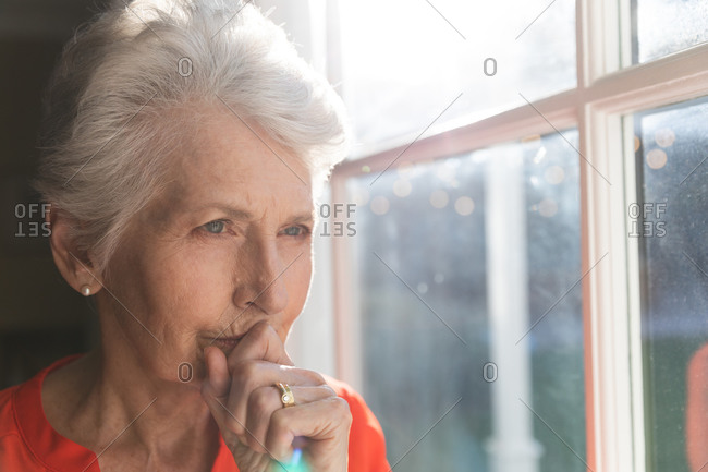Close up of a retired senior Caucasian woman at home sitting in her living room on a sunny day, looking out of the window and thinking, self isolating during coronavirus covid19 pandemic