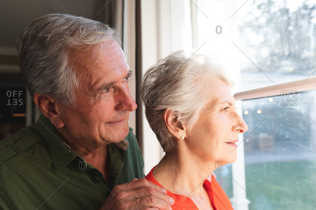 Happy retired senior Caucasian couple at home, embracing and smiling while looking out of the window together, couple at home together isolating during coronavirus covid19 pandemic