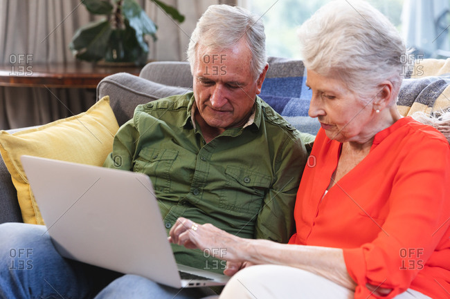 Close up of a retired senior Caucasian couple at home sitting on a sofa in their living room, talking and using a laptop computer together, couple isolating during coronavirus covid19 pandemic