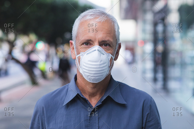 Portrait of a senior Caucasian man out and about in the city streets during the day, wearing a face mask against coronavirus, covid 19.