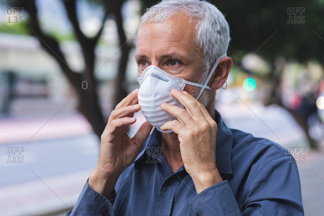 Senior Caucasian man out and about in the city streets during the day, wearing a face mask against coronavirus, covid 19.putting on face mask against air pollution and coronavirus.