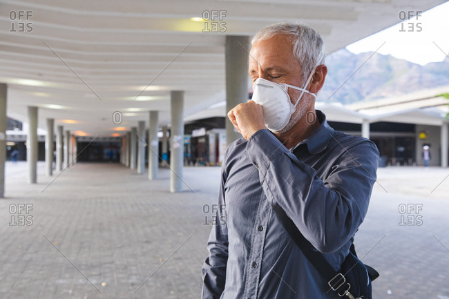 Senior Caucasian man out and about in the city streets during the day, wearing a face mask against coronavirus, covid 19, covering his face while coughing.