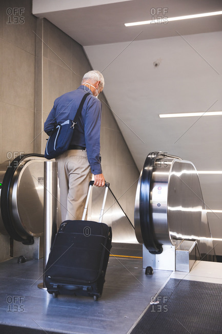 Senior Caucasian man, wearing a face mask against coronavirus, covid 19, , entering an escalator in a metro station, pulling a suitcase.