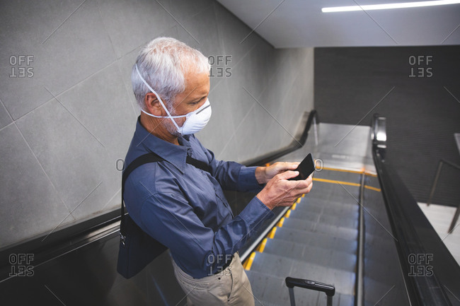 Senior Caucasian man, wearing a face mask against coronavirus, covid 19, standing on an escalator in a metro station and using his smartphone.