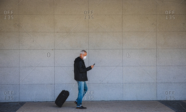 Senior Caucasian man out and about in the city streets during the day, wearing a face mask against coronavirus, covid 19, using a smartphone and pulling a suitcase.