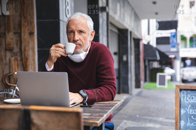 Senior Caucasian man sitting at a table at a coffee terrace, wearing a face mask against coronavirus, covid 19, drinking coffee and using a laptop computer.