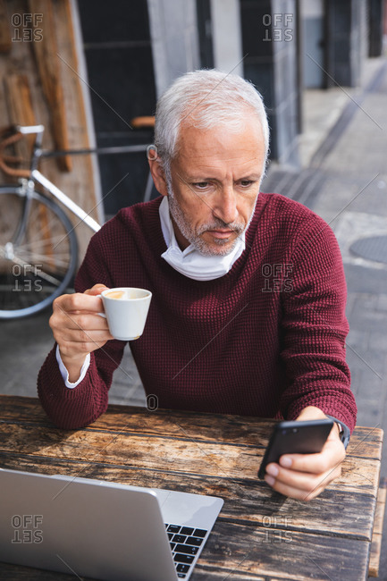 Senior Caucasian man sitting at a table at a coffee terrace, wearing a face mask against coronavirus, covid 19, drinking coffee and using a smartphone.