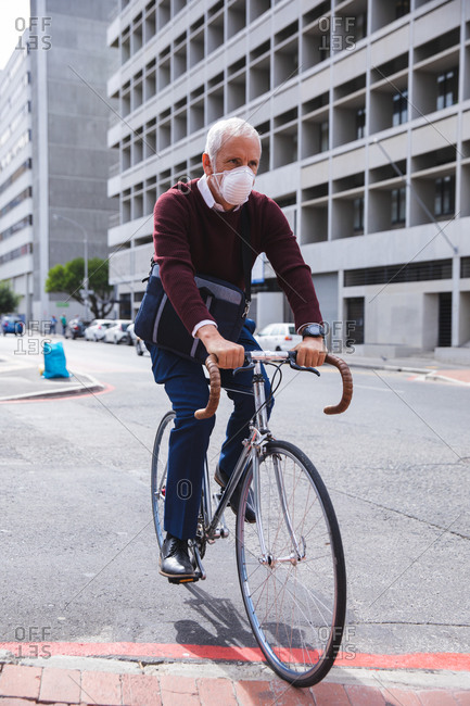 Senior Caucasian man out and about in the city streets during the day, wearing a face mask against coronavirus, covid 19, riding his bicycle.