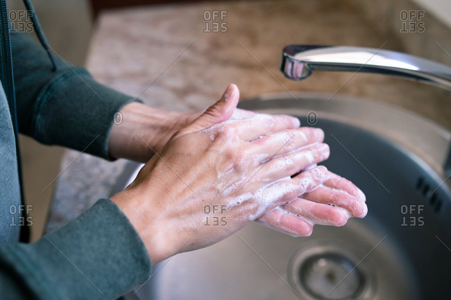 Hands of Caucasian woman at home in bathroom using soap to wash her hands in a sink close up