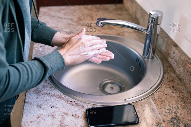 Close up of a Caucasian woman at home in bathroom during daytime washing her hands with soap in a sink