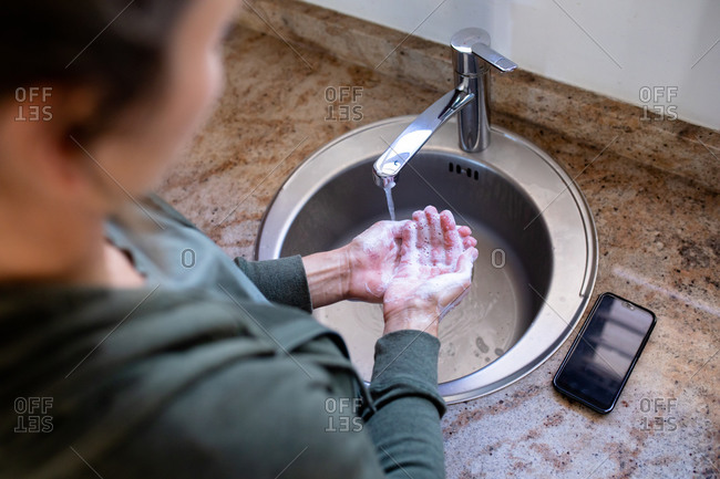 Overhead view of a Caucasian woman at home in bathroom during daytime washing her hands with soap in a sink