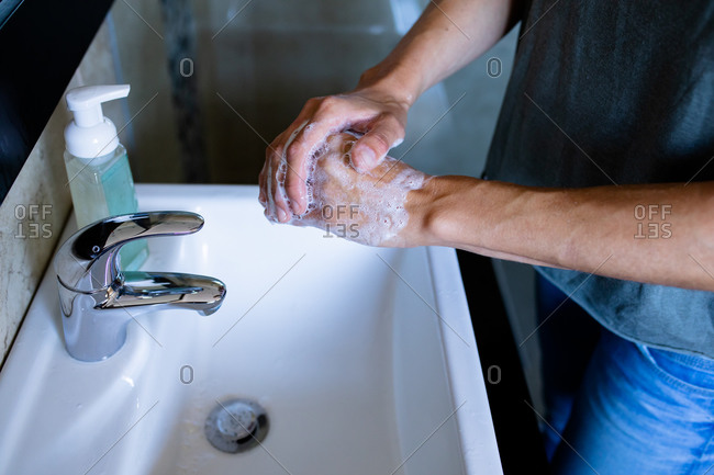 Mid section of a Caucasian woman at home in bathroom during daytime washing her hands in a basin using soap, bottle with liquid soap next to her, protection against coronavirus Covid-19 infection and pandemic. Social distancing and self isolation in quarantine lockdown