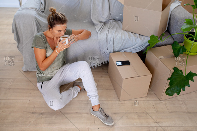 Caucasian woman spending time at home self isolating and social distancing in quarantine lockdown during coronavirus covid 19 epidemic, sitting on the floor, drinking coffee while renovating her home.