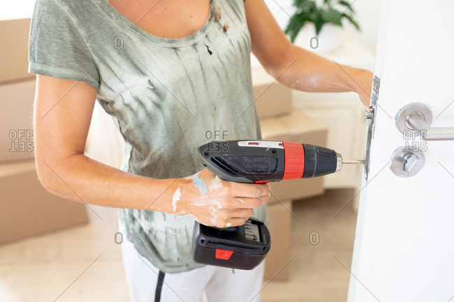 Mid section of a Caucasian woman spending time at home self isolating and social distancing in quarantine lockdown during coronavirus covid 19 epidemic, fixing the door while renovating her house.