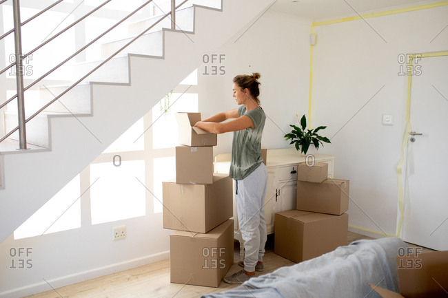 Caucasian woman spending time at home self isolating and social distancing in quarantine lockdown during coronavirus covid 19 epidemic, unpacking belongings from carton boxes.