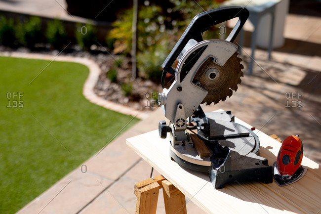 Close up of a circular saw standing on a workbench in a garden on a sunny day, during DIY while social distancing and self isolation in quarantine lockdown during coronavirus covid 19 epidemic.
