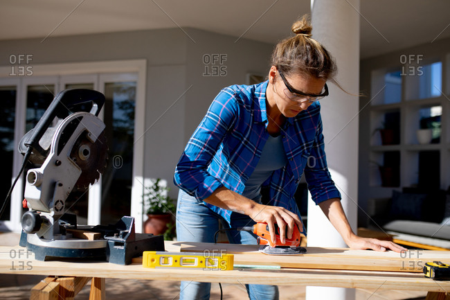 Caucasian woman spending time at home self isolating and social distancing in quarantine lockdown during coronavirus covid 19 epidemic, Caucasian woman spending time at home self isolating and social distancing in quarantine lockdown during coronavirus covid 19 epidemic, doing DIY in her garden, sanding wooden boards.