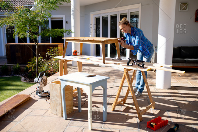 Caucasian woman spending time at home self isolating and social distancing in quarantine lockdown during coronavirus covid 19 epidemic, Caucasian woman spending time at home self isolating and social distancing in quarantine lockdown during coronavirus covid 19 epidemic, doing DIY in her garden, drilling wooden table.