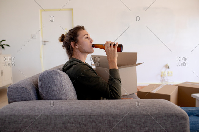Caucasian woman spending time at home self isolating and social distancing in quarantine lockdown during coronavirus covid 19 epidemic, taking a break while doing DIY, resting on a sofa and drinking a beer.