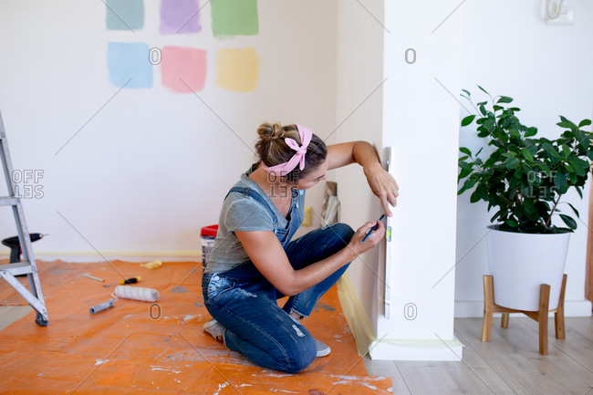 Caucasian woman spending time at home self isolating and social distancing in quarantine lockdown during coronavirus covid 19 epidemic, doing DIY, using a spirit level.