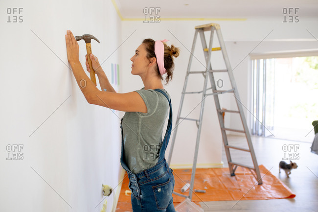 Caucasian woman spending time at home self isolating and social distancing in quarantine lockdown during coronavirus covid 19 epidemic, doing DIY at home, using a hammer.