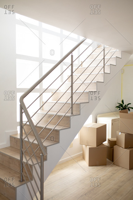 White stairs in a modern apartment during renovation, with carton boxes in the background, while social distancing and self isolation in quarantine lockdown during coronavirus covid 19 epidemic.