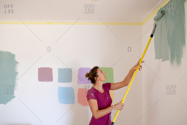Caucasian woman spending time at home self isolating and social distancing in quarantine lockdown during coronavirus covid 19 epidemic, painting the walls of her home.