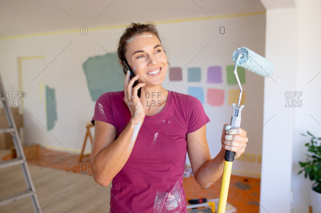 Caucasian woman spending time at home self isolating and social distancing in quarantine lockdown during coronavirus covid 19 epidemic, using her smartphone while painting the walls of her home.