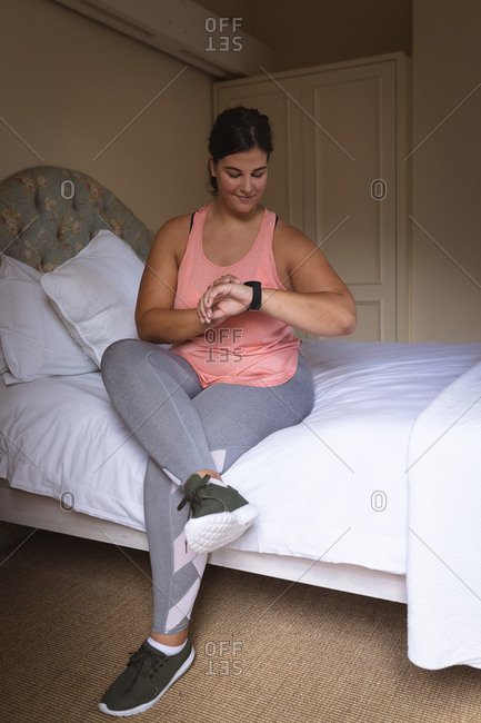 Caucasian female vlogger at home in her bedroom, preparing to demonstrate exercises for her online blog, using her smartwatch. Social distancing and self isolation in quarantine lockdown.