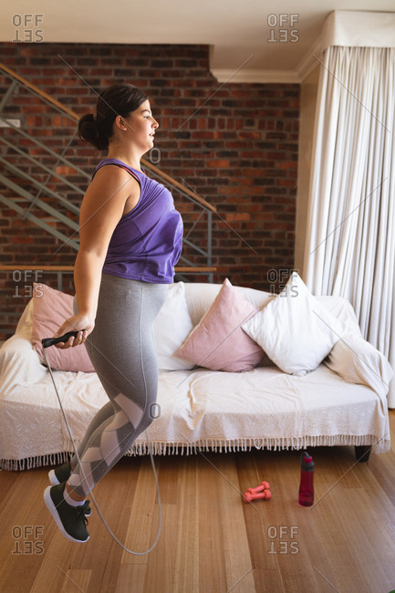 Caucasian female vlogger at home in her sitting room, demonstrating exercises with a jumping rope for her online blog. Social distancing and self isolation in quarantine lockdown.
