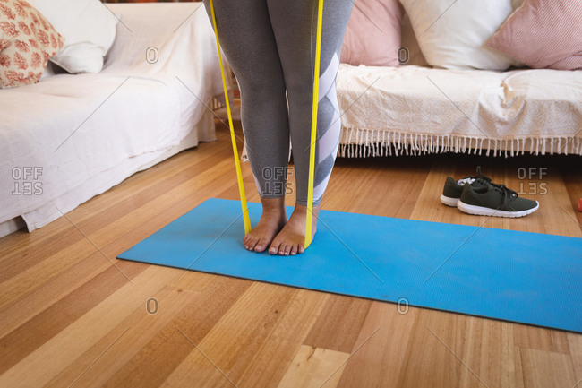 Low section of a Caucasian female vlogger at home in her sitting room, demonstrating exercises with a stretching tape for her online blog. Social distancing and self isolation in quarantine lockdown.