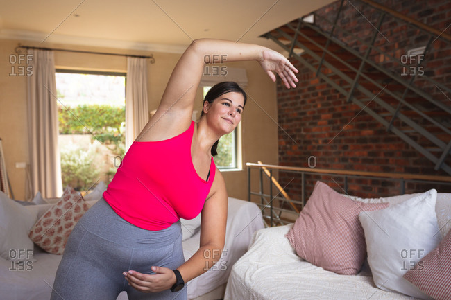 Caucasian female vlogger at home in her sitting room, demonstrating stretching exercise for her online blog. Social distancing and self isolation in quarantine lockdown.