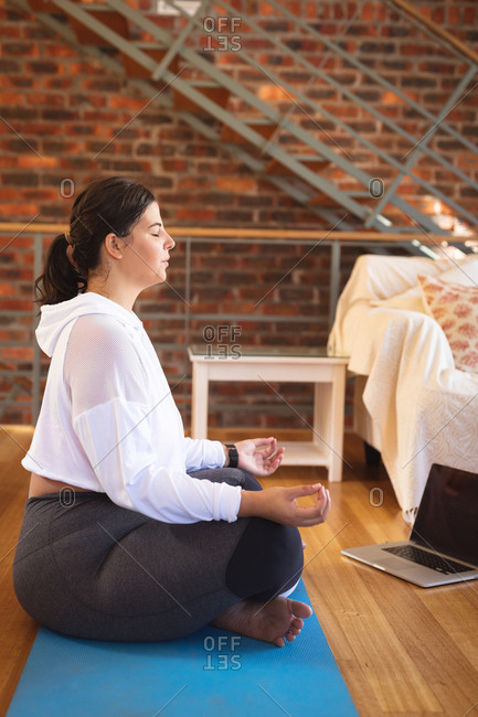 Caucasian female vlogger at home in her sitting room, practicing yoga and using her laptop computer. Social distancing and self isolation in quarantine lockdown.
