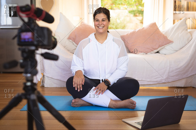 Caucasian female vlogger at home in her sitting room, demonstrating exercises for her online blog recording with a camera. Social distancing and self isolation in quarantine lockdown.