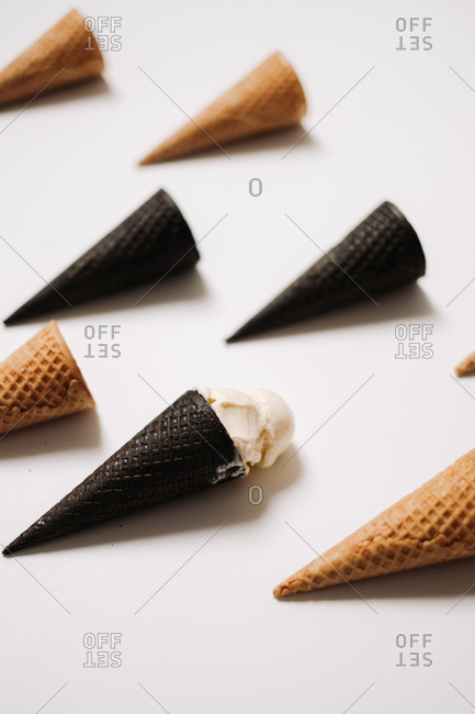 Chocolate and plain sugar cones with ice cream on white background