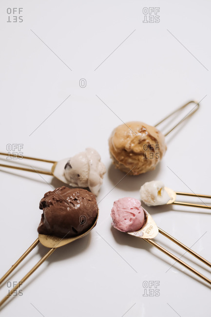 Spoons with various flavors of ice cream on white background