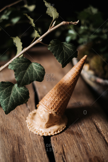 Sugar cone with ice cream and a wafer crisp on wooden surface