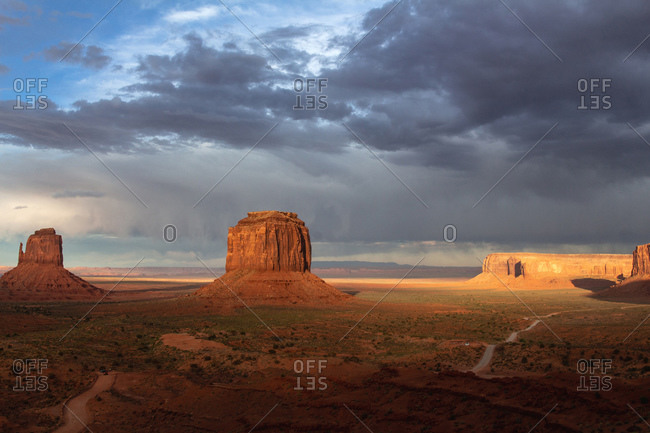 A storm leaving the scenic view of The Mittens and Merrick Butte at sunset in the Oljato Navajo Monument Valley, Arizona USA