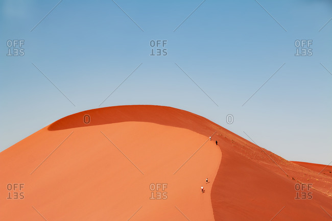 Group of people climbing the Dune 45 to the top, Namib Naukluft National Park, Namibia, Africa