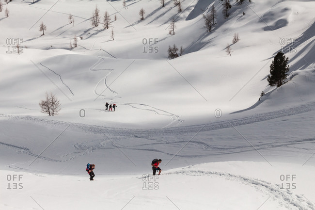 Cortina d'Ampezzo, Italy -  February 24, 2018: Hikers with snowshoes walking on the path near Cinque Torri peaks in a winter day