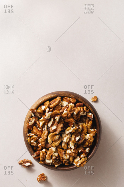 Wooden bowl with peeled walnuts top view