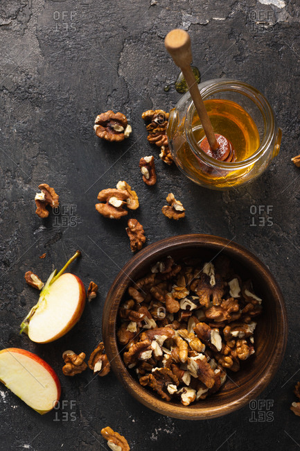 Wooden bowl with peeled walnuts, jar of honey and apple top view