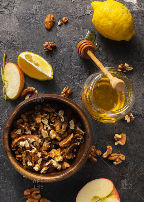 Healthy products for Immunity boosting. Wooden bowl with peeled walnuts, jar of honey, apple and lemon top view.