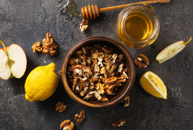 Wooden bowl with peeled walnuts, jar of honey, apple and lemon top view. Healthy products for Immunity boosting