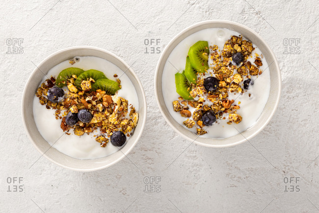 Bowl of diet food with granola with kiwi, blueberries, nuts and yogurt top view