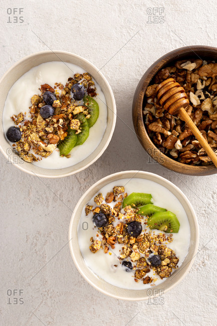 Bowl granola with kiwi, blueberries and yogurt top view