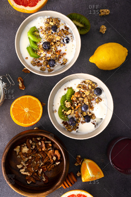 Bowl of diet food with granola with kiwi, blueberries, nuts and vegan yogurt top view